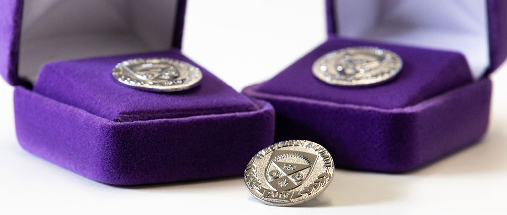 Photo of Western Class of 2019 pins with purple velvet.