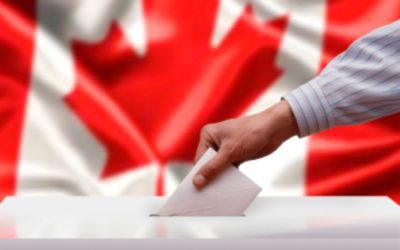 Voter's hand drops a ballot into the box in front of a canadian flag