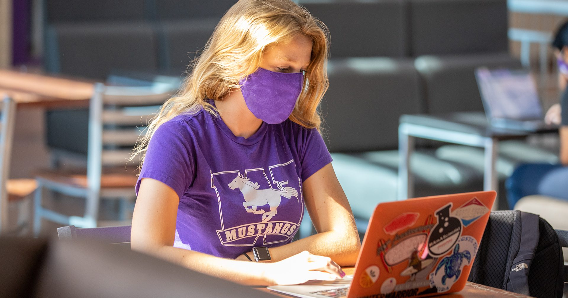 student wearing mask at laptop computer